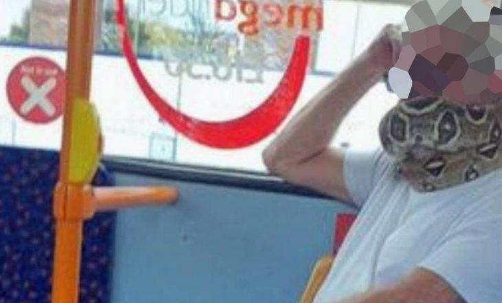 Një burrë shihet në autobus me një gjarpër të gjallë si maskë për fytyrë