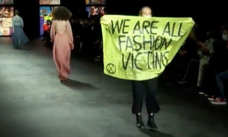 """Sfilata e Dior ndërpritet nga një protestues me pankartën që shkruan """"Ne të gjithë jemi viktima të modës"""""""